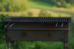Empty portable BBQ grill in front of a fresh green summer landsc Royalty Free Stock Images