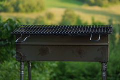 Empty portable BBQ grill in front of a fresh green summer landscape Royalty Free Stock Images