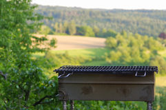 Empty portable BBQ grill in front of a fresh green summer landscape Royalty Free Stock Photography