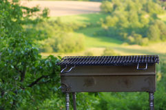 Empty portable BBQ grill in front of a fresh green summer landscape, close-up Royalty Free Stock Photos
