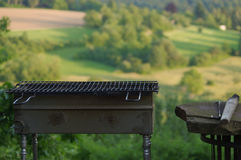 Empty portable BBQ grill in front of a fresh green summer landscape, close-up Stock Photography
