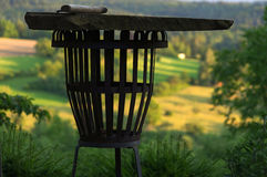 Empty portable BBQ grill in front of a fresh green summer landscape, colse-up Royalty Free Stock Image