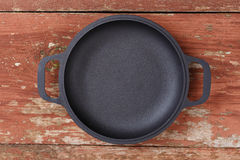 Empty portioned frying pan on a wooden background. Stock Images