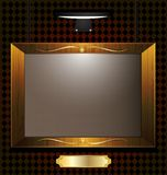 Empty portrait. On the darkened wall lit by wall lamps empty picture frame, beneath a golden plate Stock Images