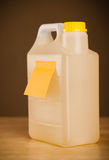 Empty post-it note sticked on gallon. Gallon with empty sticky note Royalty Free Stock Photos