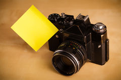 Empty post-it note sticked on photo camera Stock Photography