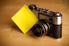 Empty post-it note sticked on photo camera Royalty Free Stock Photo