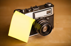 Empty post-it note sticked on photo camera Stock Image