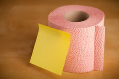 Empty post-it note sticked on toilet paper. Toilet paper roll with empty sticky note Royalty Free Stock Image