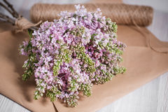 Empty postal envelope and bouquet of lilac flowers on the white wooden background, copy space. Top view. Stock Photos
