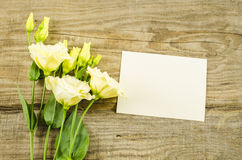 Empty postcard and colorful flowers on wooden background Royalty Free Stock Image