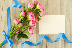 Empty postcard, flower and blue ribbon on wooden background Stock Photo