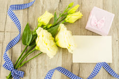 Empty postcard, flower and blue ribbon on wooden background Royalty Free Stock Photos