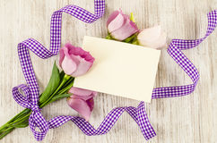 Empty postcard, flower and purple ribbon on wooden background Royalty Free Stock Image