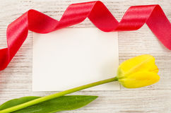 Empty postcard with flower and red ribbon on wooden background Royalty Free Stock Photo