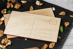 An empty postcard on a wooden background. Cinnamon, walnuts and a romantic note. Invitation, celebration concept. Copy. Cute composition of wooden postcards on a Stock Photos
