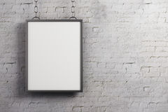 Empty poster on brick wall. Empty rectangular poster hanging on white brick wall background. Gallery, advertising, exhibition concept. Mock up, 3D Rendering Stock Photography