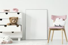 Empty poster with place for your picture standing on the floor i. N bright kid room interior with white cupboard and pink chair royalty free stock photo