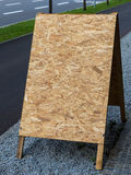 Empty poster stand. An empty poster stand made of pressed wood shavings. copy space and background Stock Photo