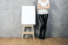 Empty poster on stool. Woman with empty poster on stool standing in room with concrete wall and wooden floor. Advertising concept. Mock up Royalty Free Stock Photo