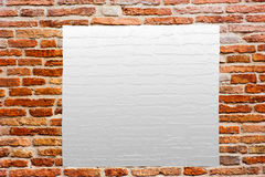 Empty poster on the wall. Ancient brick wall with glued blank poster Stock Photo