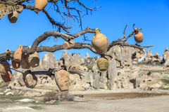 Empty pots, hanging on a tree on a background of mountains of Ca. Empty pots, hanging on a tree on a background of mountains. Turkey. Capadocia Royalty Free Stock Images