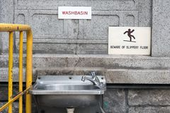 The empty public bathroom in Hong Kong. Steel sink hang on stone wall on street in city center. The empty public bathroom in Hong Kong Stock Photos