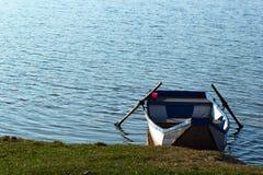 Empty punt boat at lake`s shore.  Royalty Free Stock Photos