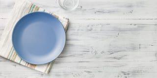 Empty purple plate on wooden background. Empty purple plate on light wooden background Royalty Free Stock Photo