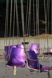 Empty purple seats hanging from chains Royalty Free Stock Photo