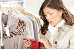 Empty purse or wallet - no money for shopping. Concept. Woman shopping for clothing in clothes store Stock Images