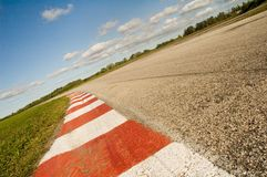Empty race track. Coloured curb on an empty race track in a sunny day. Warmer tones royalty free stock photos