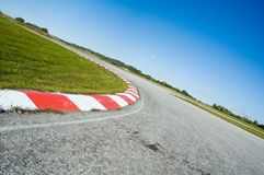 Empty race track. Coloured curb on an empty racetrack in a sunny day stock photography