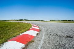 Empty race track. Coloured curb on an empty race track in a sunny day royalty free stock photo