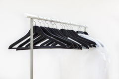 Empty rack with hanging black hangers and bags for clothes Royalty Free Stock Photo