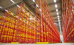 Empty racks in warehouse. Huge warehouse inside with empty racks in red Royalty Free Stock Images