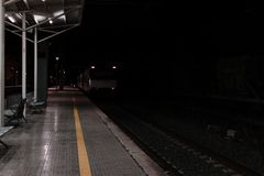 Empty rail road station at night. The train is going on the tracks stock photos