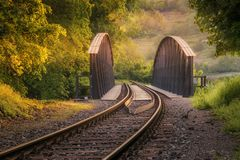 Empty railroad forest at sunset. Wonderful atmospheric landscape. Empty railroad forest at sunset. Railway track in golden sunlight. Gold sunbeams. Wonderful royalty free stock photo