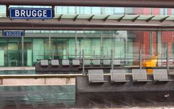 Empty railway station building and platform with glass walls and sign Brugge and waiting bench with seats. Travel concept Royalty Free Stock Photos