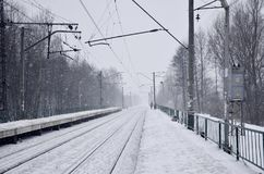Empty railway station in heavy snowfall with thick fog. Railway rails go away in a white fog of snow. The concept of the railway Royalty Free Stock Photography