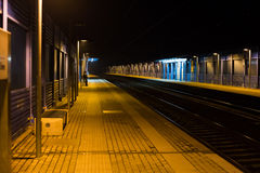 Empty railway station at night with a single person waiting the Royalty Free Stock Images