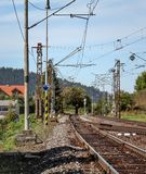 Empty railway tracks on a sunny summer day, in rural area, pillars with many electric cables around. stock photography