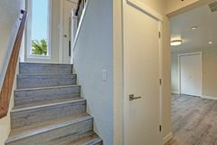 Empty rambler style home features gray wood staircase stock image