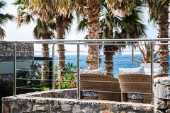 Empty rattan chairs on a resort`s balcony facing the sea stock photography