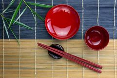 Empty red bowls with red chopsticks on holder and bamboo leaves placed on bamboo mat royalty free stock photography