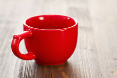 Empty red ceramic cup. On brown wooden background Stock Photo