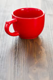 Empty red ceramic cup. On brown wooden background Stock Photography
