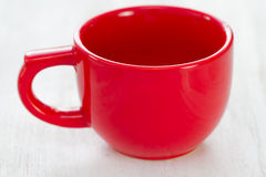 Empty red ceramic cup on white. Wooden background Royalty Free Stock Images