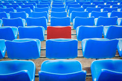 An empty red chair, arounded by blue chairs at the football Stad Stock Photo