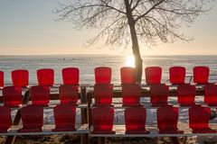 Winter morning on the river. Empty red chairs beach stadium in the winter morning Royalty Free Stock Photos